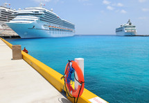 Cruise ships docked at a pier in a blue ocean.