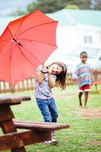 girl child with a red umbrella