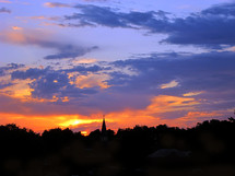 Vivid sunset silhouettes church steeple with cross.