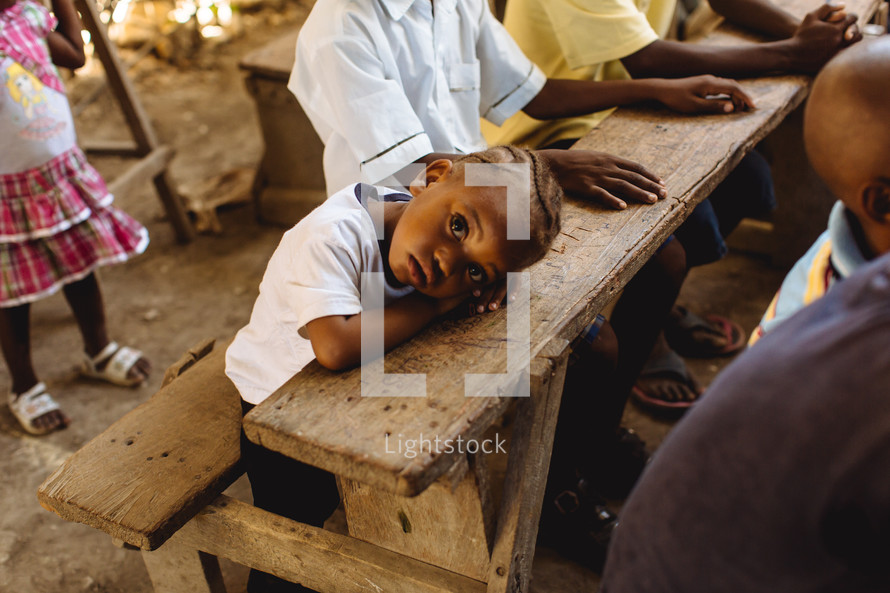 a child with his head on a desk in a classroom in Haiti
