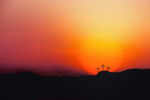 Sunset over three crosses on a hill.