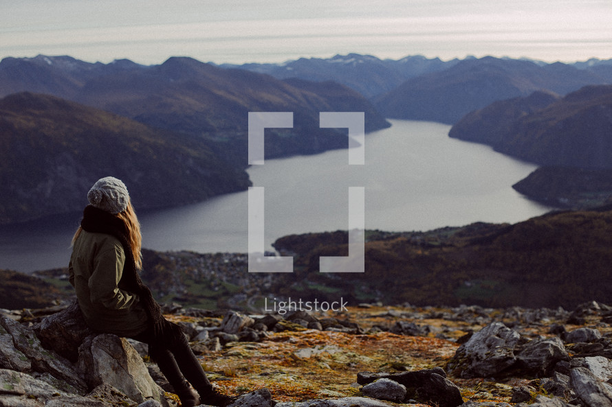 woman looking out at a fjord below