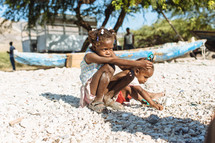 children sitting on a beach in Haiti