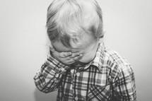 toddler boy playing peek-a-boo