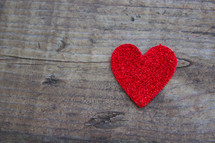 A single red heart on a rugged wooden board.