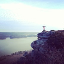 woman jumping in the air standing on a rock ledge near a lake