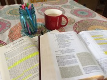 jar of pens, open Bible, journal, and coffee mug on a table