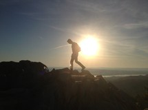 Silhouette of man hiking on a mountain ridge at sunset.