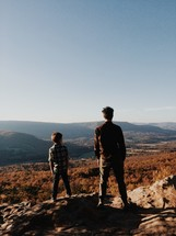 a father and son looking out at mountains