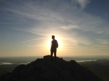 silhouette of a man on top of a mountain