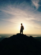 silhouette of a man at the top of a mountain