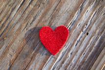 A single heart on a rugged board.