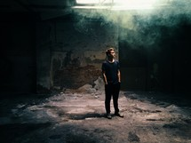 man standing in an abandoned building and smoke