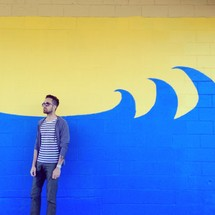 man standing in front of a wall with a wave painted on it
