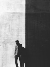 man and his shadow on a black and white wall