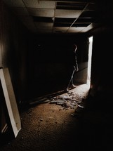 A man walking out of a dark, abandoned room.