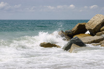 seascape with background for text. Scenic beautiful morning surf on the rocky shore under cloudy heaven