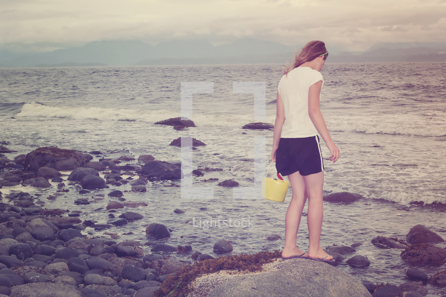 girl with a sand bucket walking on a rocky beach