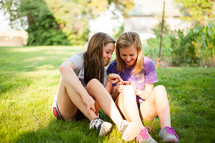 Teens engaging together while looking at a phone.