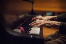 Elderly hands playing the piano.