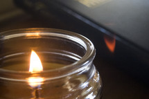 flame on a candle and hymnal