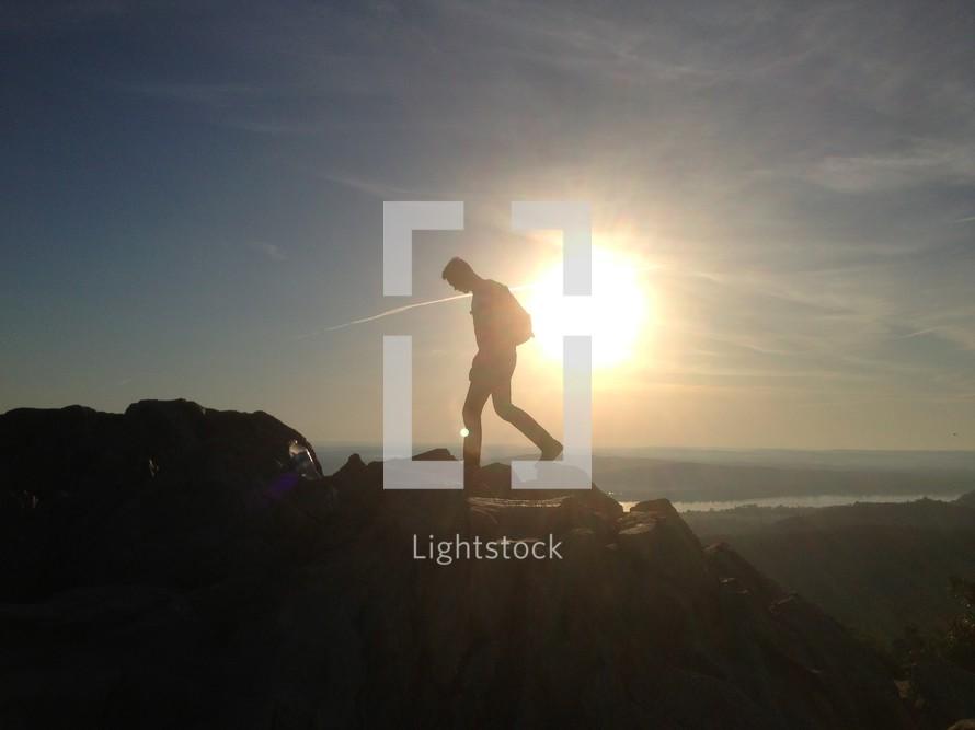 Silhouette of man hiking on a mountain ridge at sunset.