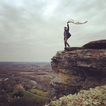 man holding a scarf blowing in the wind standing at the top of a mountain