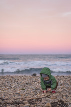 toddler playing with rocks on a beach