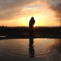 Silhouette of person at sunset with reflection in the water.