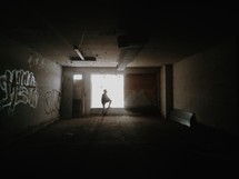 A silhouette of a person standing before a bright window in an empty room.