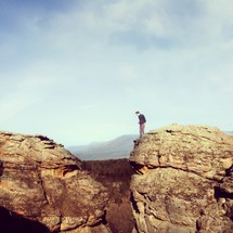 Man standing on mountain top, looking down in the valley between two boulders.