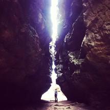 sunlight shining on a man standing between two cliffs