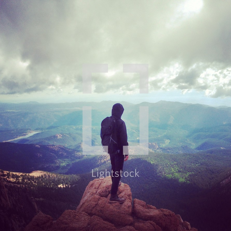 Back of a man standing on a mountain top looking down into a valley.