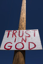 """Trust in God"" sign nailed to a telephone pole."