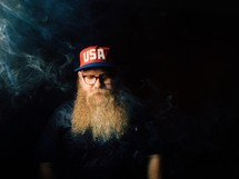 man with a long beard and smoke