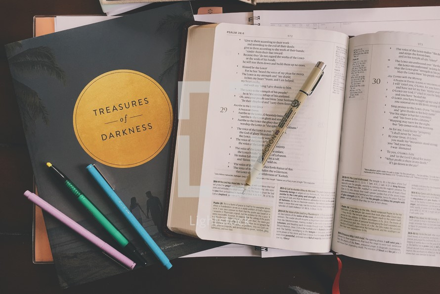 Treasures of darkness book, pens, and open Bible