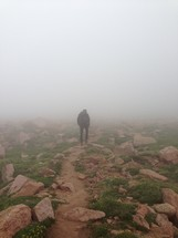 man walking through thick fog