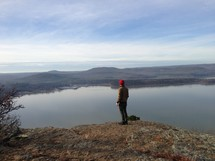 man standing at the edge of a mountain top looking out over a lake