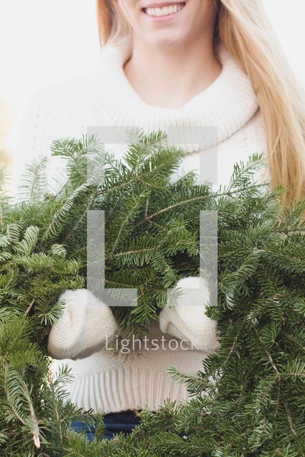 woman holding a Christmas wreath