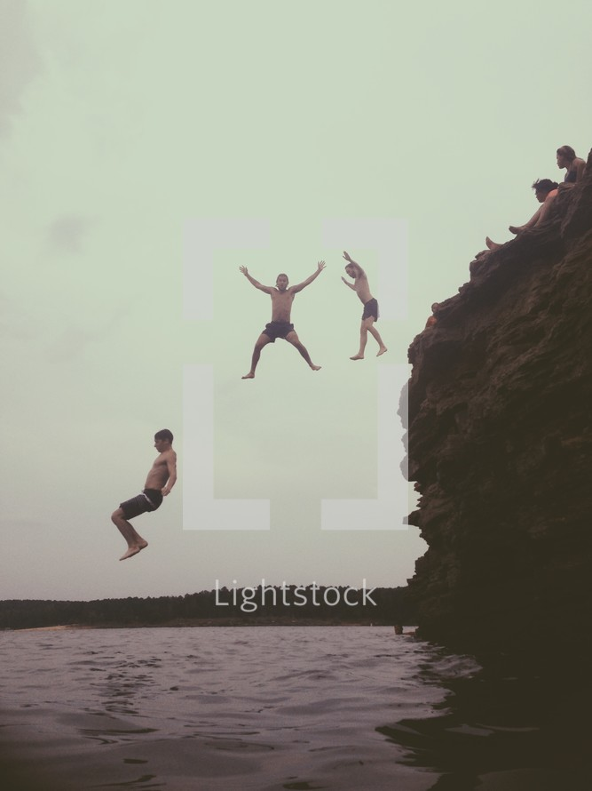 men jumping off a cliff into water
