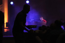 Silhouette of a man passing metal trays to the audience at a concert.