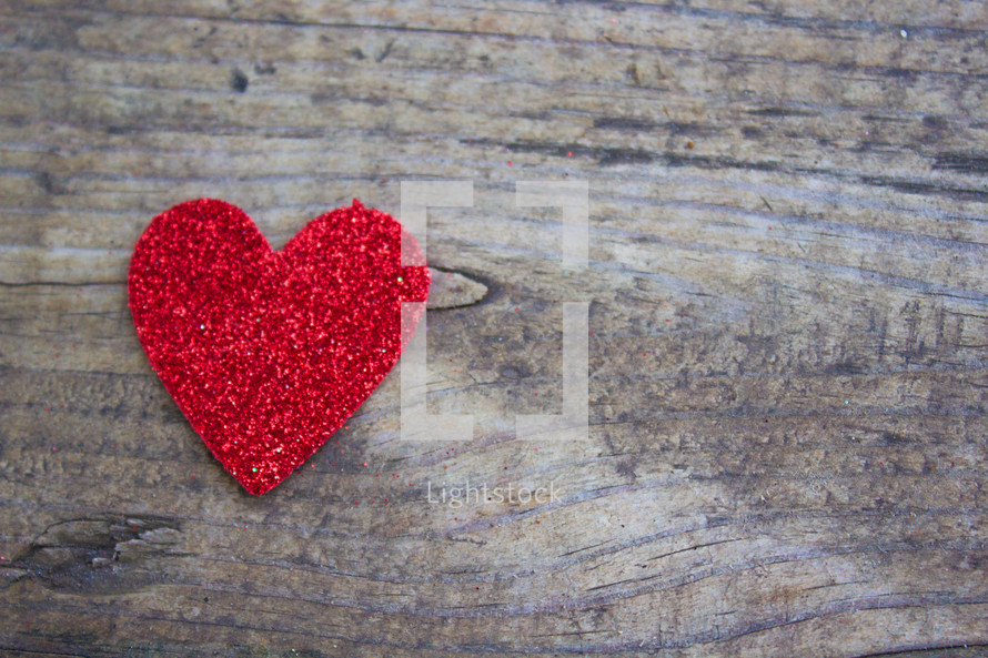 A single red heart on a rugged wood board.