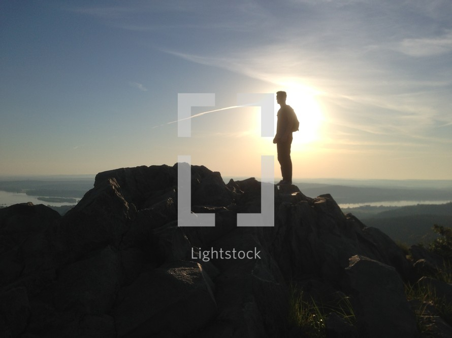silhouette of a man on a mountain top at sunrise