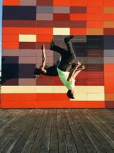 Two men doing back flips in front of a colorful wall.