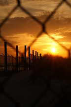 chain link fence and barbed wire at sunset