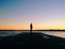 man standing at the end of a dock