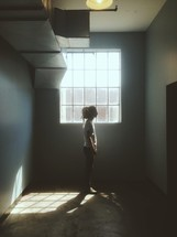 Girl standing alone in front of a window in an empty room.