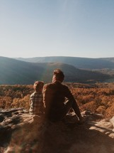 a father sitting with his son outdoors on a mountaintop