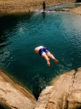 man diving off a cliff into a water hole