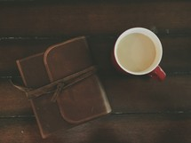 A cup of coffee and a leather journal on a wooden table.